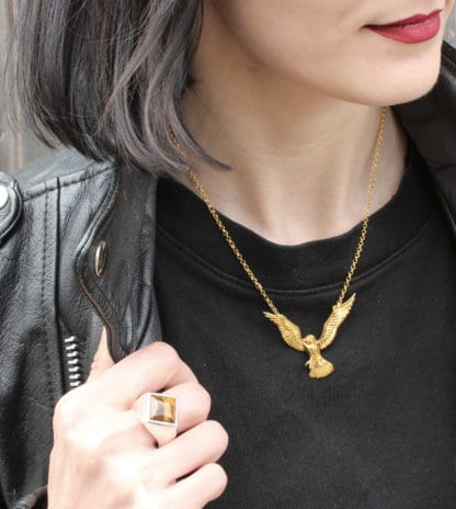 woman with red lips and black hair wearing a yellow gold flying barn owl necklace and a square tiger eye ring